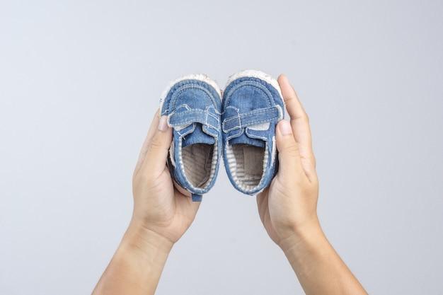 Mano che tiene vecchie e strappate scarpe da bambino come un simbolo per la memoria preziosa