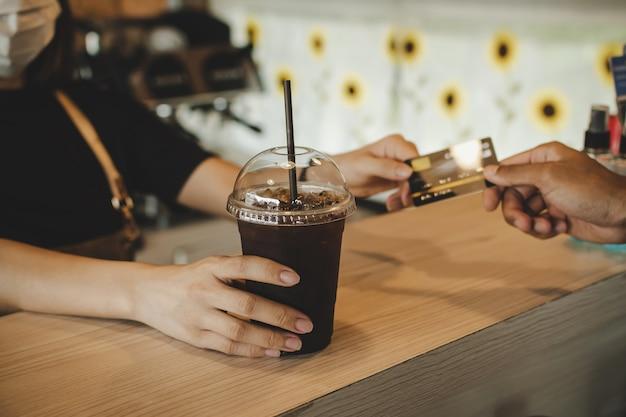 Mano cliente pagando con carta di credito per l'acquisto di caffè nero ghiaccio sul bancone nella moderna caffetteria caffetteria, ristorante caffetteria, pagamento digitale, piccolo imprenditore, cibo da asporto, concetto di cibo e bevande