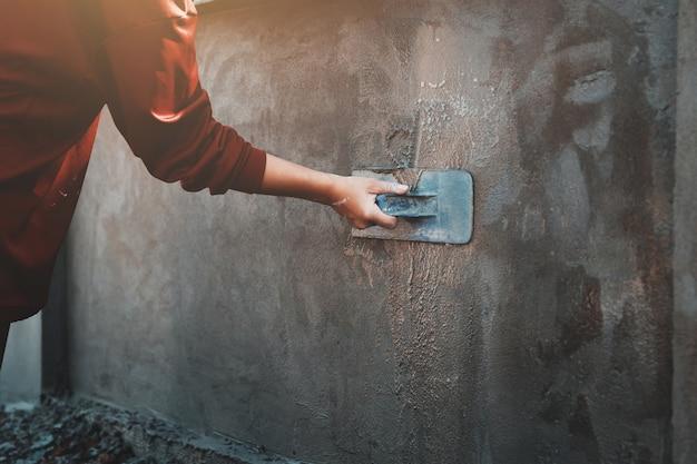 Mano closup degli operai che intonacano sulla parete all'aperto al cantiere