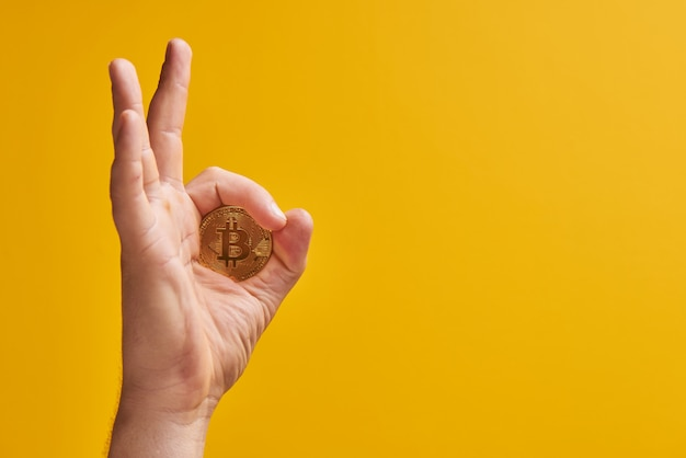 Mano con bitcoin moneta fisica su sfondo giallo, gesto
