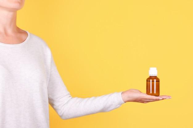 Mano con bottiglia di medicina, contenitore di chimica isolato