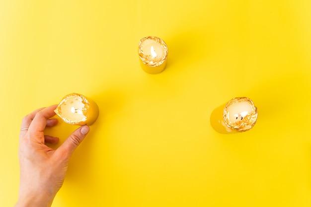 Mano con candele d'oro su superficie gialla. wellnes, magia, concetto di relax.