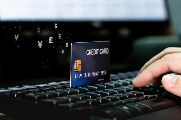Mano con carta di credito sulla tastiera con flusso icona valuta denaro.