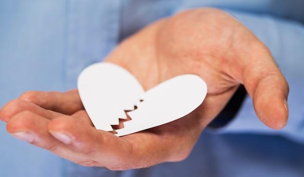 Mano con cuore di carta rotto