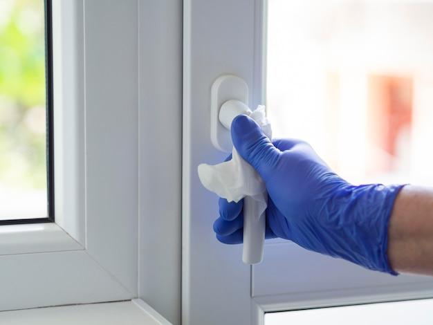 Mano con guanto chirurgico per la pulizia della maniglia della finestra con un tovagliolo