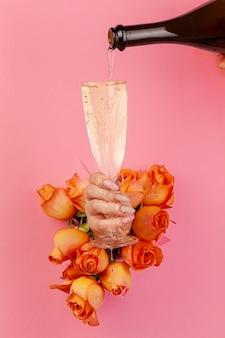 Mano con manicure versando champagne in un bicchiere attraverso un buco in una carta strappata decorata con rose