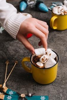 Mano con marshmallow vicino a coppa e giocattoli di natale