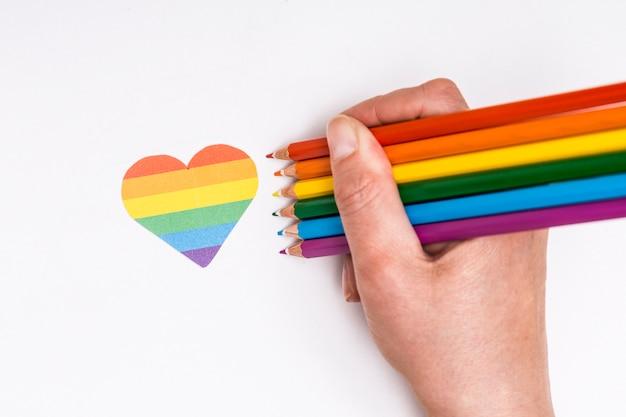 Mano con matite colorate e icona del cuore come segno lgbt