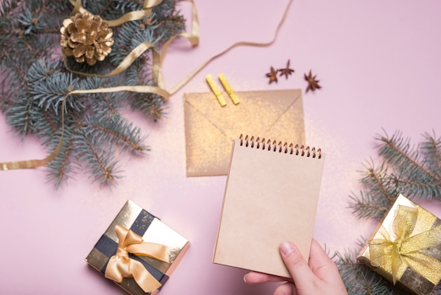 Mano con notebook vicino a scatole presenti, ramoscelli di abete, busta e nastro