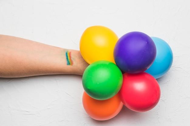 Mano con palloncini e strisce nei colori lgbt