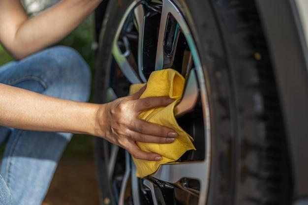 Mano con panno in microfibra per la pulizia della ruota dell'auto
