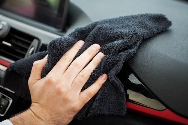 Mano con panno in microfibra per pulizia interni auto