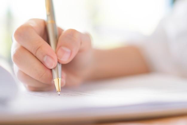 Mano con penna sopra forma di domanda