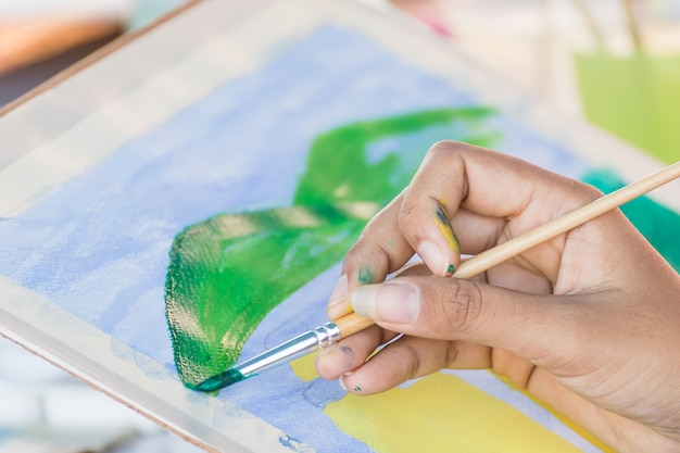Mano con pennello e vernice di acquerelli