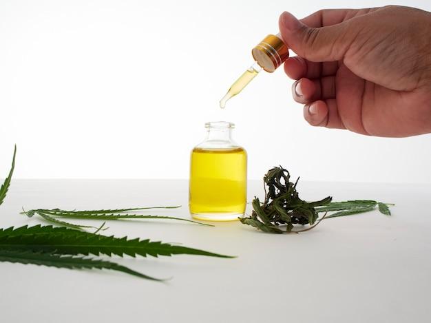 Mano con pipette e olio di estratto di cannabis.