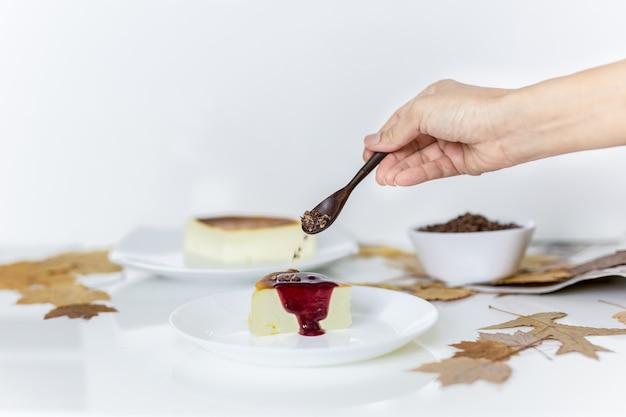 Mano con un cucchiaio di legno mettendo pennini di cacao sulla cheesecake.