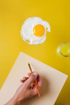 Mano con un pennello e un foglio di carta bianco disegna uova fritte, accanto a un barattolo di acqua gialla