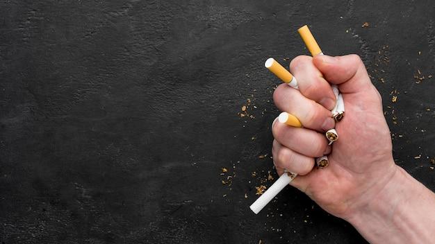 Mano copia-spazio con le sigarette