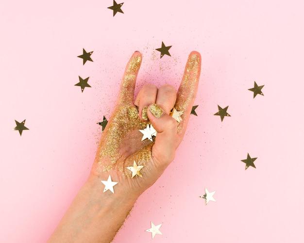 Mano creativa del primo piano con le stelle dorate