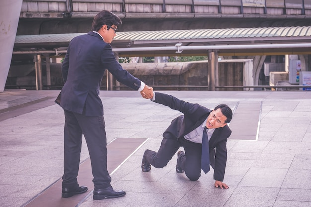 Mano d'aiuto dell'uomo d'affari nel concetto di affari