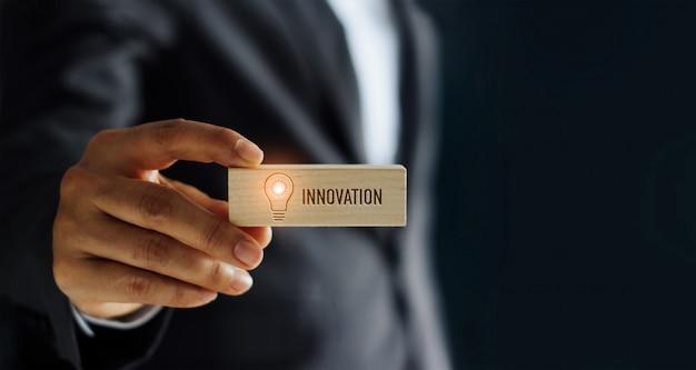 Mano d'ardore della lampadina dell'icona della tenuta dell'uomo d'affari e parola dell'innovazione in blocco di legno