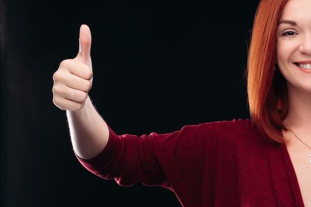 Mano dai capelli rossi attraente della tenuta della donna con i pollici su.