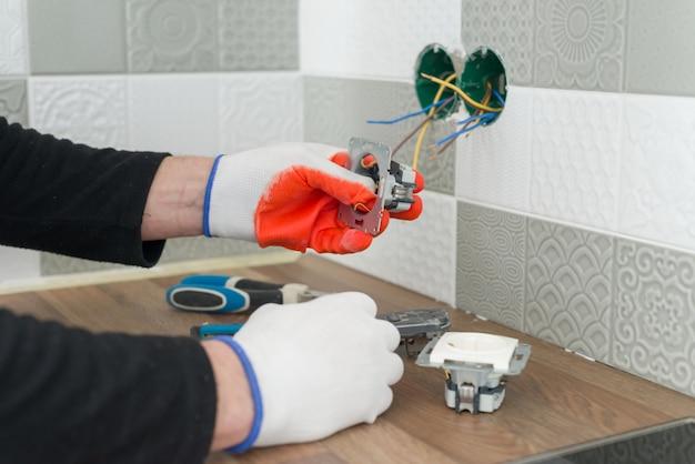 Mano degli elettricisti che installa presa sulla parete con piastrelle di ceramica