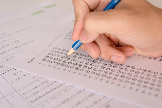 Mano degli studenti che tiene la matita scrivendo la scelta selezionata su fogli di risposta e domande di matematica