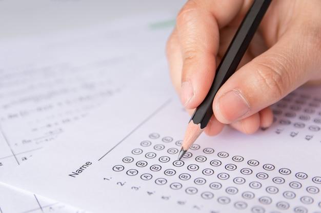 Mano degli studenti che tiene la matita scrivendo la scelta selezionata sui fogli di risposta e sui fogli delle domande di matematica. studenti che stanno facendo esami. esame scolastico
