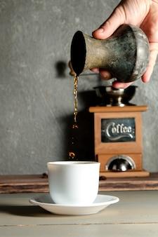 Mano degli uomini che versa una tazza di caffè che crea spruzzata