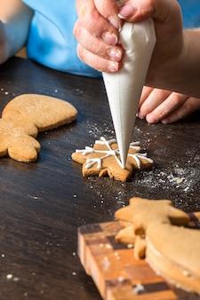 Mano dei bambini che decora i biscotti con zucchero