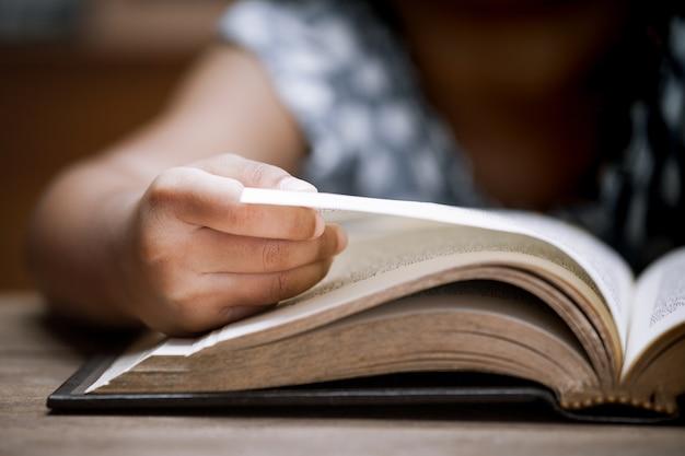 Mano del bambino del primo piano che apre e che legge un libro in biblioteca nel tono di colore d'annata