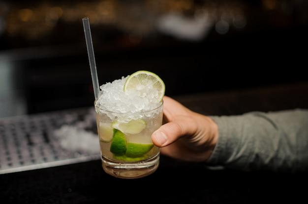 Mano del barista che tiene un bicchiere pieno di cocktail caipirinha con una cannuccia
