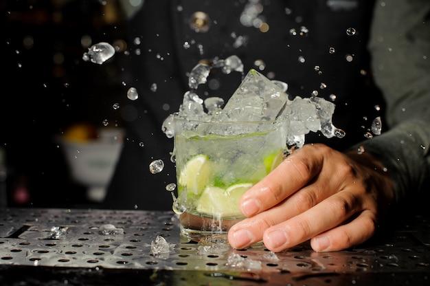 Mano del barista che tiene un bicchiere pieno di cocktail caipirinha