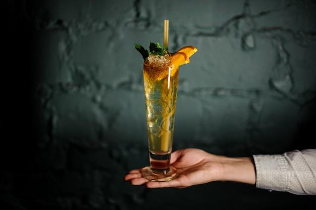 Mano del barista che tiene un cocktail estivo rosso fresco decorato con fette di menta e arancia
