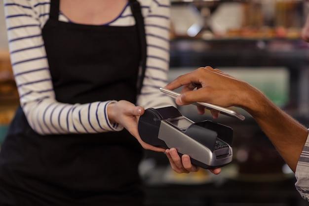 Mano del cliente che paga dal lettore della carta di credito con il suo smartphone