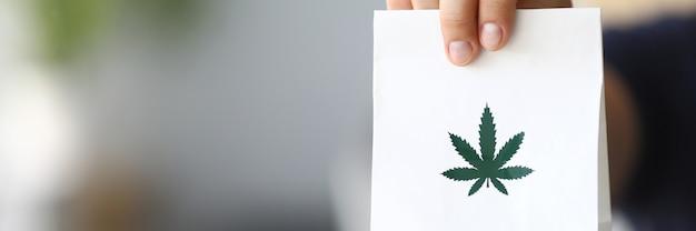 Mano del corriere che passa pacchetto con marijuana