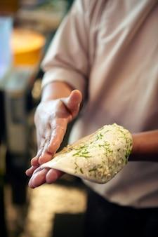 Mano del cuoco unico che prepara pasta indiana