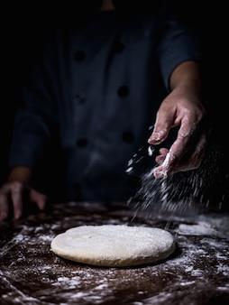 Mano del cuoco unico di pasticceria che spruzza farina bianca sopra pasta cruda sul tavolo da cucina.