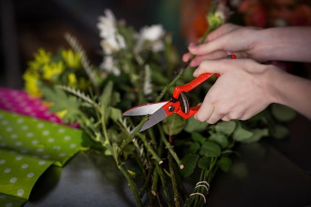 Mano del fiorista femminile che prepara il mazzo del fiore