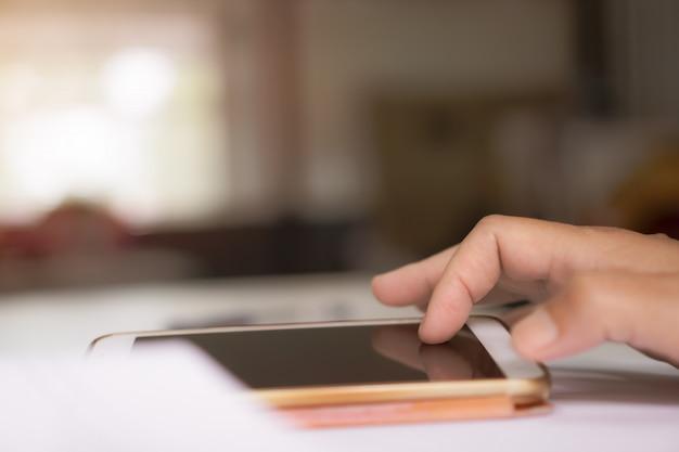 Mano del giovane che indica dito sullo smart phone dello schermo in bianco