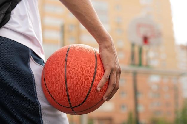 Mano del giovane giocatore di pallacanestro professionista che tiene palla mentre sta andando ad avere formazione sul campo da giuoco