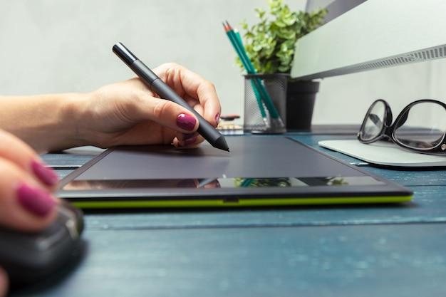 Mano del graphic designer che lavora con stilus e tablet