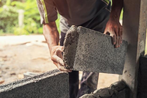 Mano del lavoratore che intonaca cemento sul muro di mattoni al cantiere