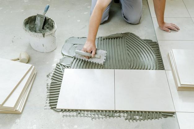 Mano del lavoratore che mette le piastrelle adesive sul pavimento con spatola dentata