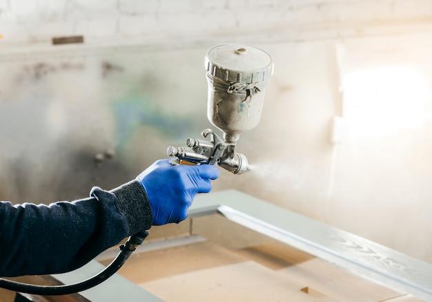 Mano del maestro pittore con pistola a spruzzo in una fabbrica