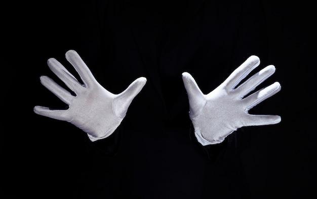 Mano del mago che indossa guanti bianchi su sfondo nero