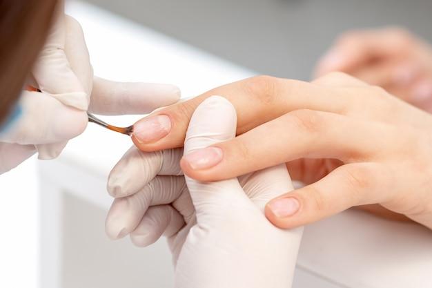 Mano del manicure applicando smalto trasparente