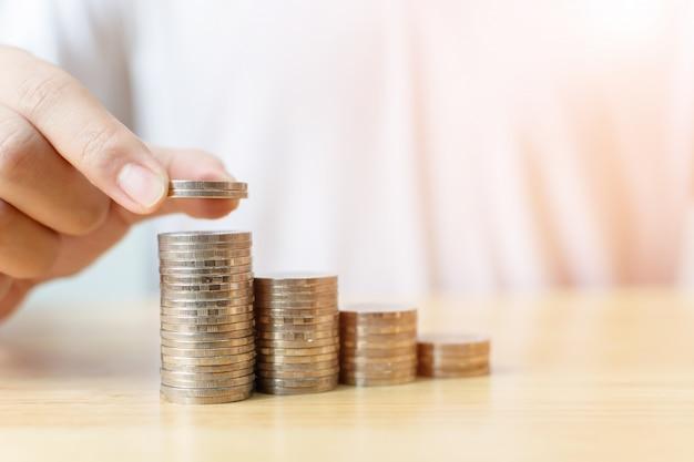 Mano del maschio che mette valore crescente di crescita di punto della pila delle monete