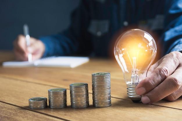 Mano del maschio che tiene una lampadina con la pila di monete e di spazio della copia